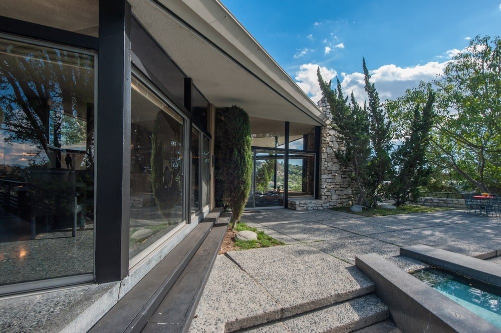 This is the back of the house showcasing the concrete set of steps leading from the glass wall of the house to the poolside area. Image courtesy of Toptenrealestatedeals.com.