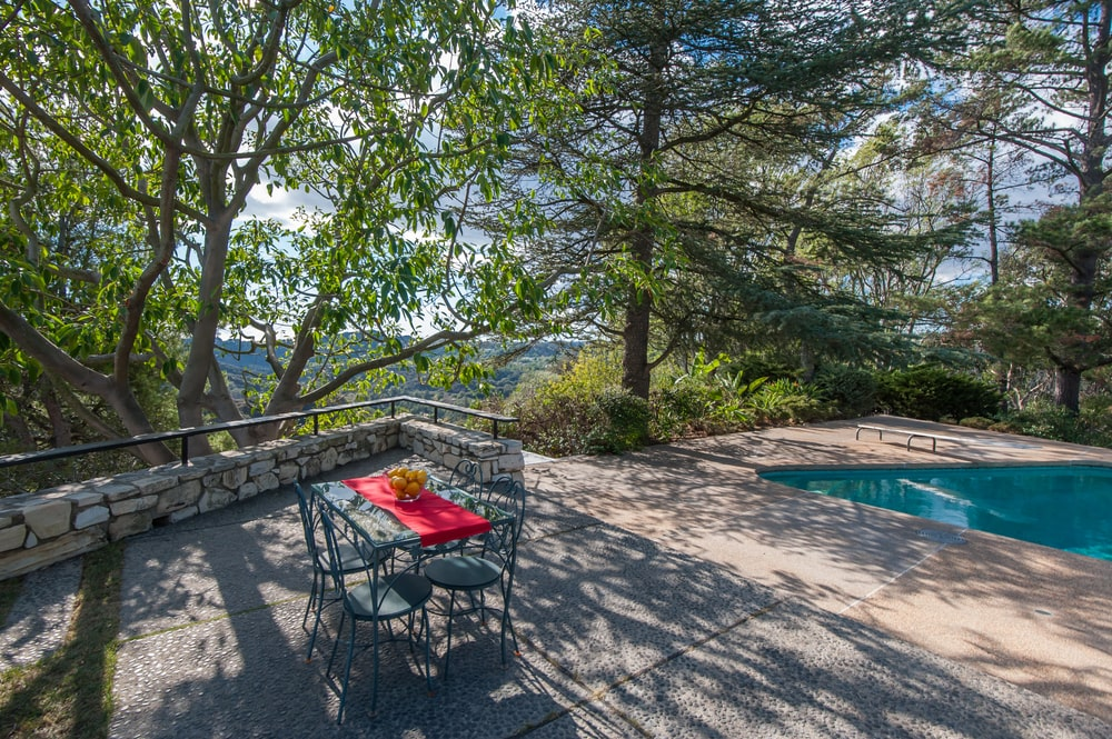 This side of the pool has an outdoor dining area shaded by tall trees. Image courtesy of Toptenrealestatedeals.com.