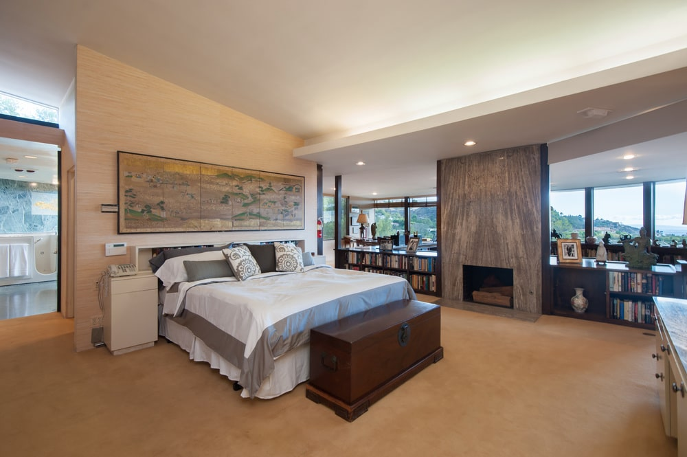 The bedroom has a beige floor that pair well with the beige walls and ceiling. These make the white bed stand out along with gray stone panel that houses the fireplace. Image courtesy of Toptenrealestatedeals.com.
