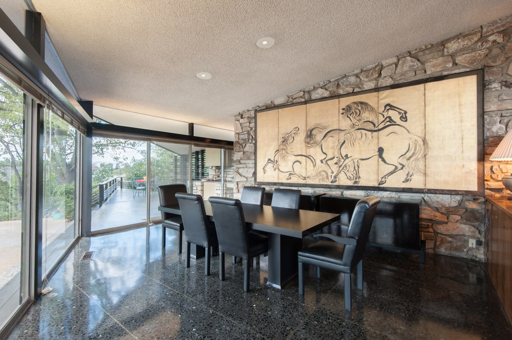 The dining room has a large black rectangular dining table surrounded by black leather chairs on a dark hardwood flooring. Image courtesy of Toptenrealestatedeals.com.