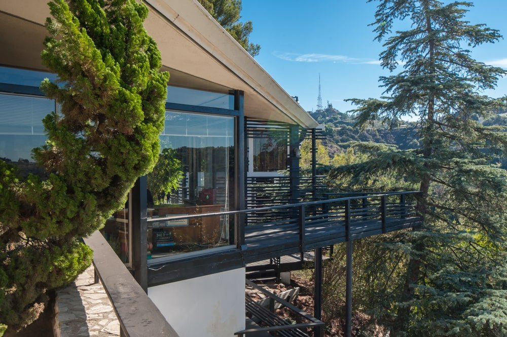 This is a look at the house exteriors from the vantage point of the balcony. You can see here the large glass walls and black frames paired with the earthy tone of the roof. Image courtesy of Toptenrealestatedeals.com.