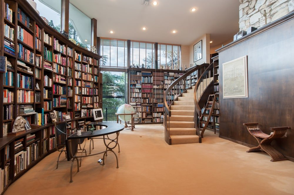 This is the library with large wooden bookshelves lining the walls adorned with glass windows above by the white ceiling. Image courtesy of Toptenrealestatedeals.com.