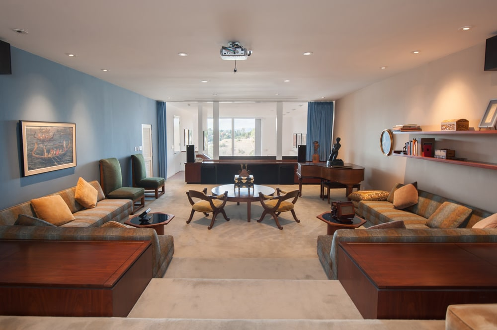 This is the living room with various sitting areas and wooden coffee tables illuminated by the large glass windows at the far end. Image courtesy of Toptenrealestatedeals.com.