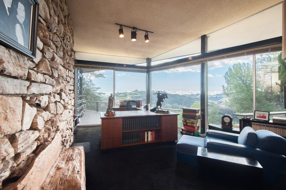 This is the home office with tall glass walls and a stone wall on one side. The wooden desk at the far end stands out against the dark flooring. Image courtesy of Toptenrealestatedeals.com.
