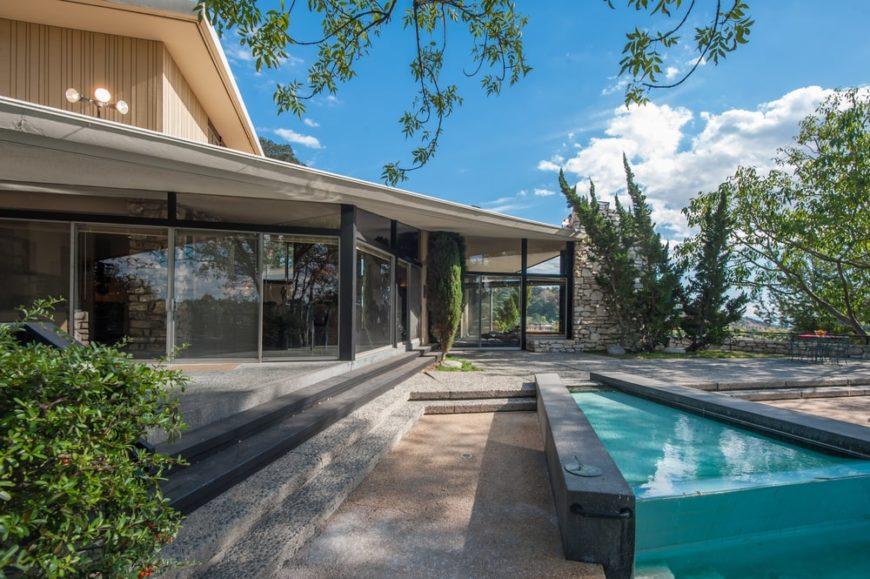 This is a view of the back of the house featuring the pool that is just a few steps away from the large glass walls of the house. Image courtesy of Toptenrealestatedeals.com.