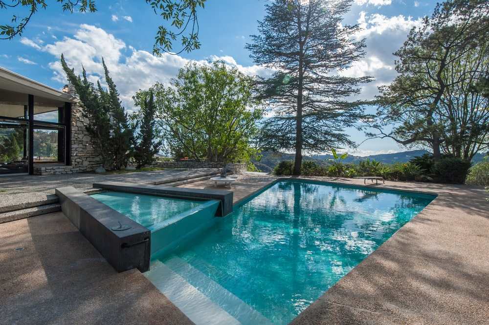 The swimming has a smaller spa pool on the side that is slightly elevated over the pool. You can also see here the concrete walkways surrounding the area. Image courtesy of Toptenrealestatedeals.com.