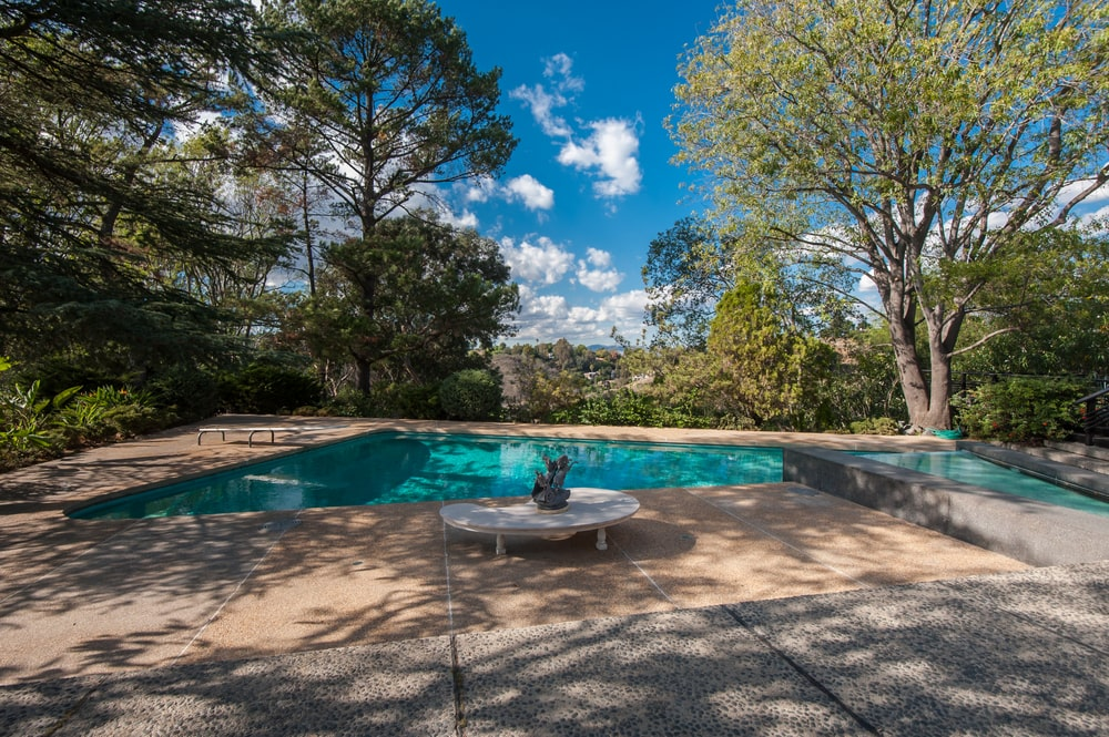 This is a close look at the backyard swimming pool adorned with tall trees that bring in a cool shade to the large area. Image courtesy of Toptenrealestatedeals.com.