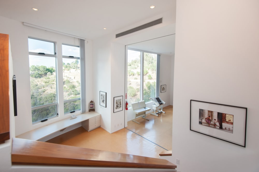 This is the artist's studio as seen from the staircase. You can see here the light hardwood flooring, white walls and white ceiling complemented by the large glass walls that bring in natural lighting. Image courtesy of Toptenrealestatedeals.com.