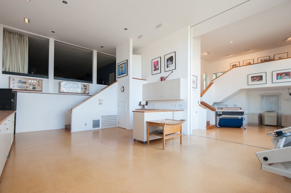This is a look at the tall ceilings and bright white walls of the artist's studio that pair well with the hardwood flooring. Image courtesy of Toptenrealestatedeals.com.