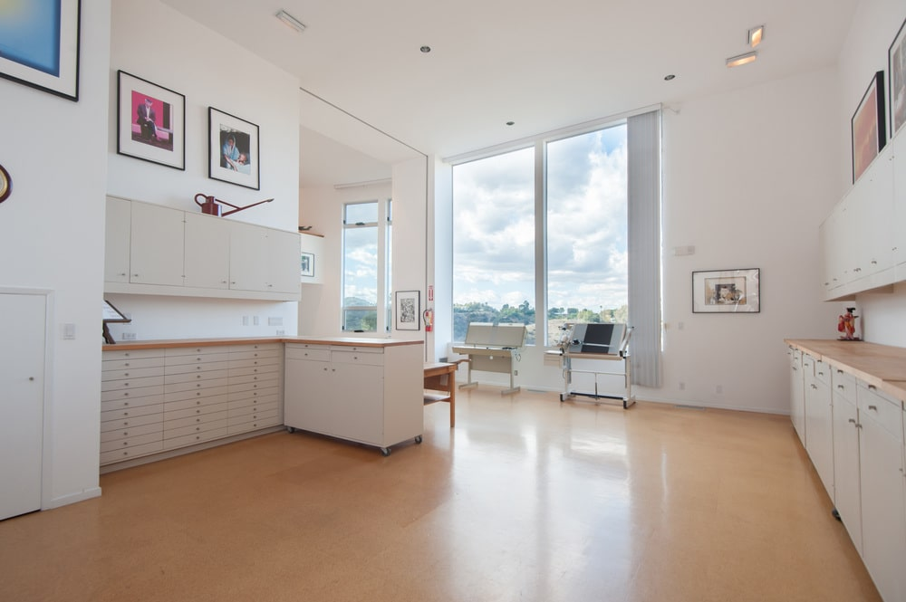 This side of the large artist's studio shows the small and bright kitchen with an L-shaped peninsula. Image courtesy of Toptenrealestatedeals.com.