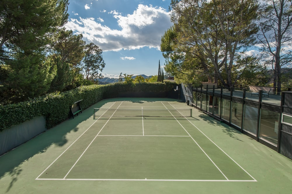 This angle of the tennis court shows the surrounding shrub hedges and tall trees. Image courtesy of Toptenrealestatedeals.com.