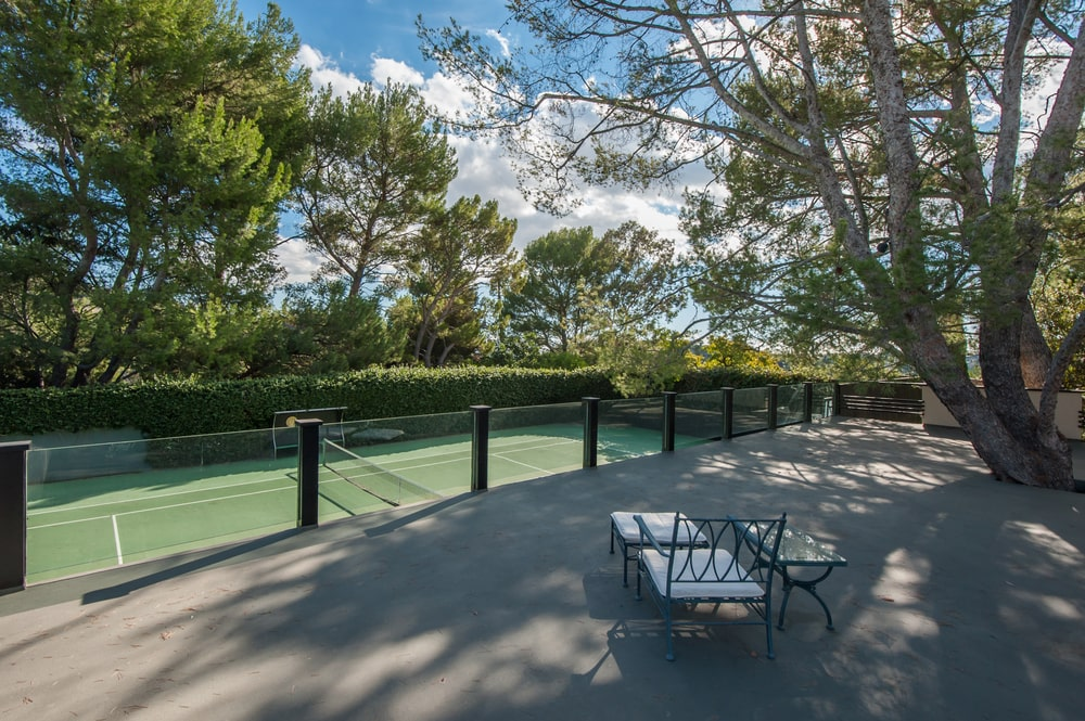 This is the balcony overlooking the tennis court fitted with a sitting area under the shade of tall trees. Image courtesy of Toptenrealestatedeals.com.