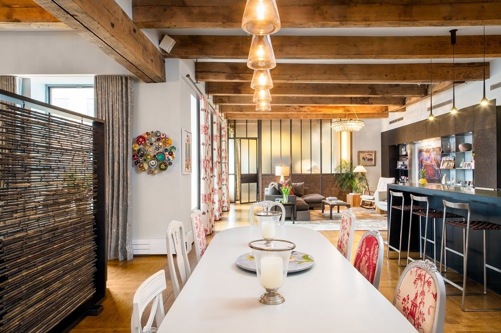 This is a close look at the dining area beside the kitchen. It has a long rectangular table topped with a row of pendant lights hanging from the ceiling that has exposed wooden beams. Image courtesy of Toptenrealestatedeals.com.