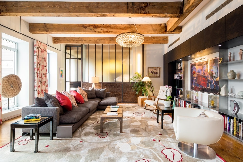 This other look at the living room shows the crystal lighting hanging from the ceiling that is dominated by exposed beams. On the far side is a frosted glass wall that separates the living room from the bedroom. Image courtesy of Toptenrealestatedeals.com.
