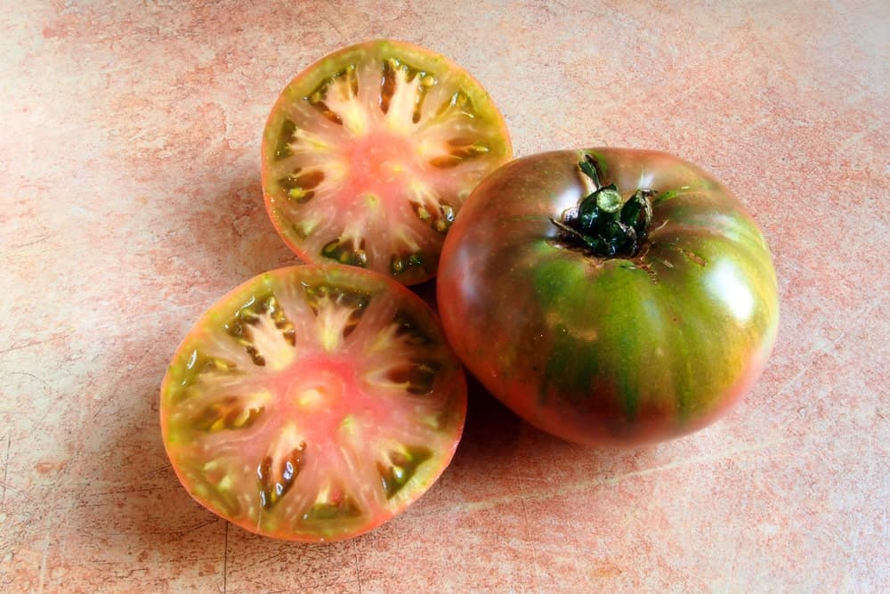 A Cherokee purple tomato with slices on the side.