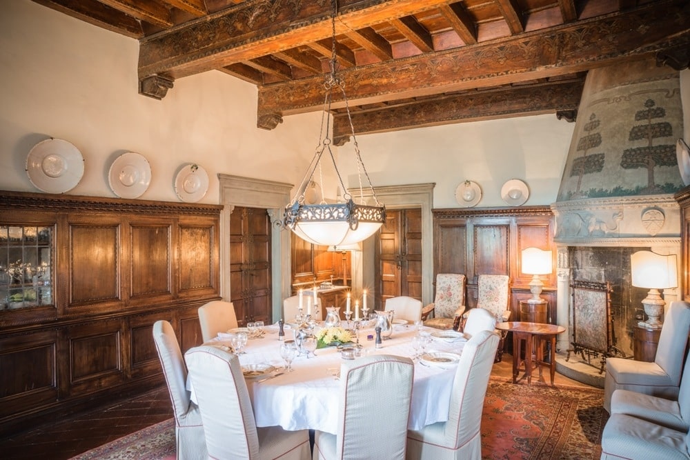 The formal dining room has a large dining table with a table cloth that matches the slipcovers of the chairs. These are then complemented by a tall wooden ceiling with exposed beams and a pendant light over the table. Image courtesy of Toptenrealestatedeals.com.