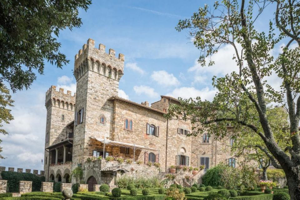 This is a front view of the castle with stone exterior walls and crenelated towers. These are complemented by the green landscaping that is filled with trees, <a class=