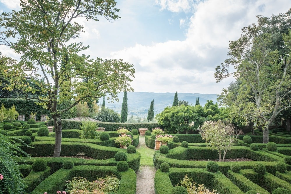 The garden has well-maintained and manicured decorative shrub hedges that form a maze adorned with tall trees. Image courtesy of Toptenrealestatedeals.com.