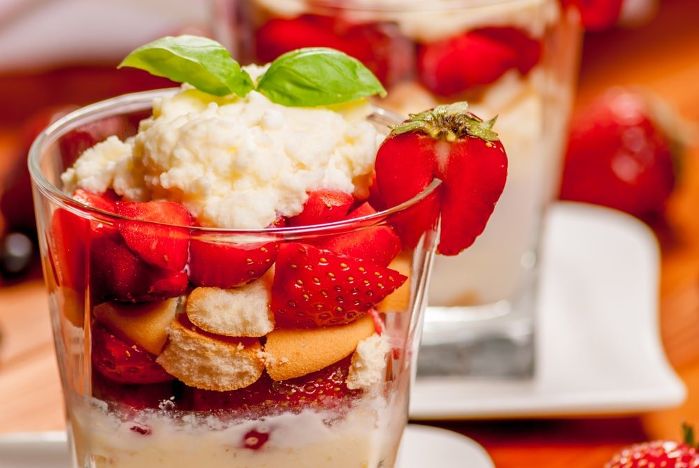 A serving of strawberry trifle in a glass.