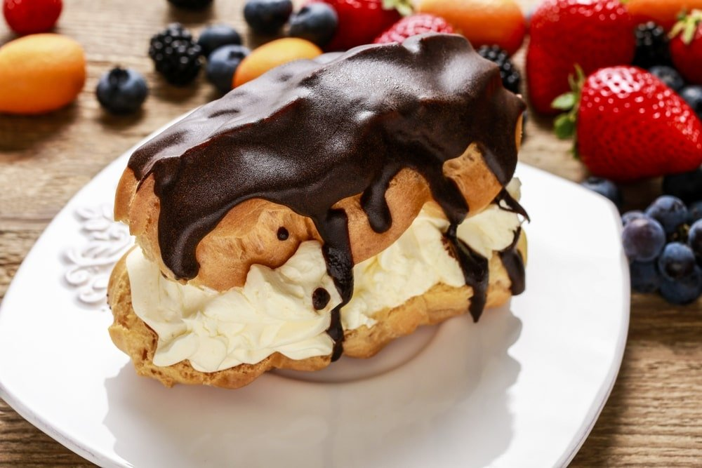A piece of chocolate eclair cake garnished with fresh fruits.