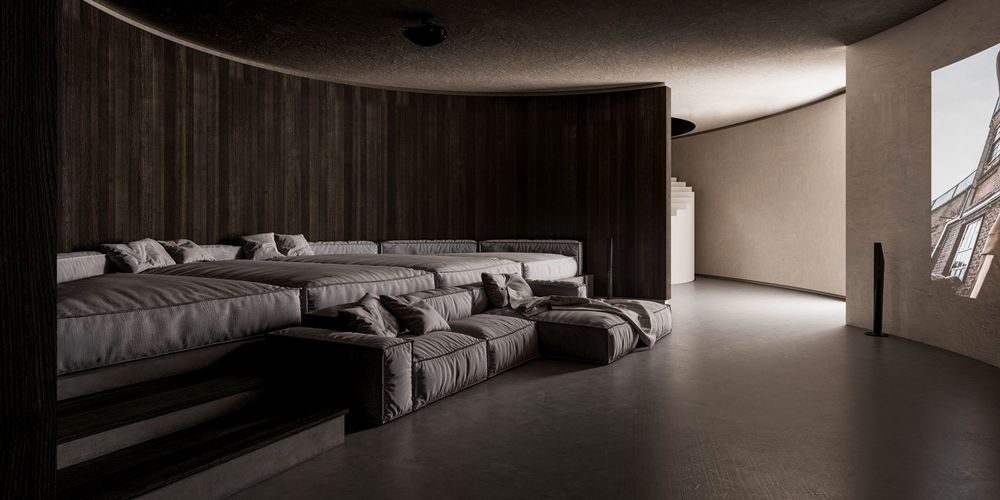 This is the home theater room with a large curved wall of projected screen across from gray sectional couches and daybeds combined to create a comfortable cushioned space surrounded by a dark curved wall.