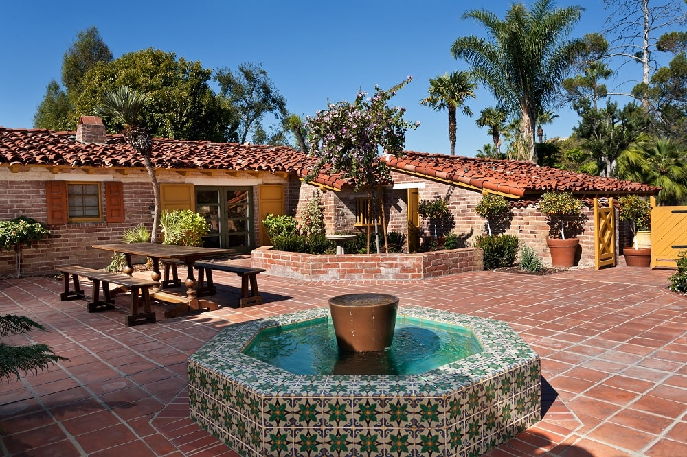 This is the large courtyard that the house surrounds. It has terracotta flooring tiles, a fountain, a garden and an outdoor dining area. Image courtesy of Toptenrealestatedeals.com.