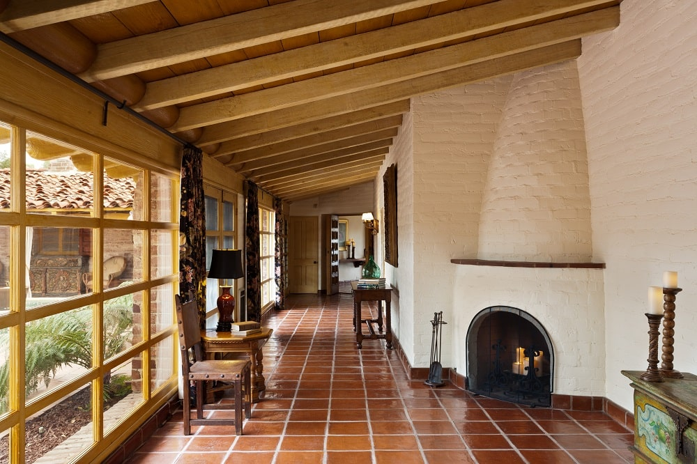 Upon entry of the house, you are welcomed by this foyer that has dark brown flooring tiles and a wooden shed ceiling with exposed beams. At the far corner is a small fireplace embedded onto the beige wall. Image courtesy of Toptenrealestatedeals.com.