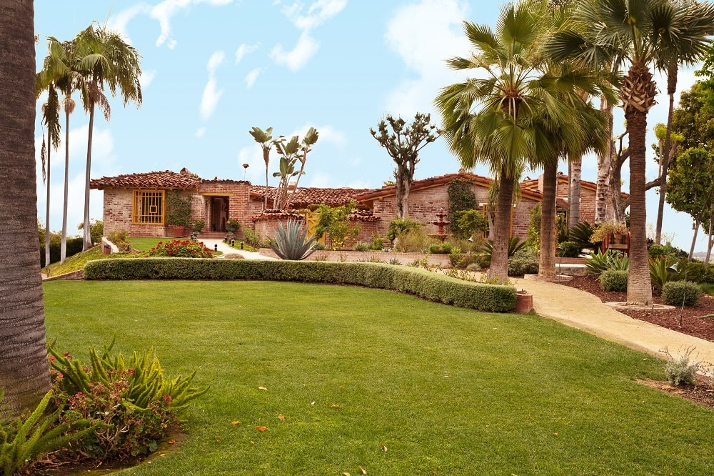 This is a front view of the house exterior with earthy tones on its exterior walls adorned by the surrounding landscape of tropical trees and various desert plants. Image courtesy of Toptenrealestatedeals.com.