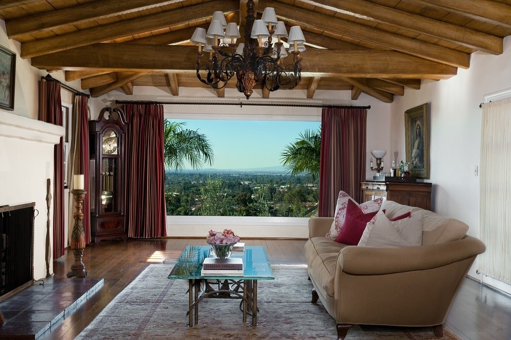 This is the living room of the house with a beige sofa facing a glass-top coffee table and a fireplace. These are complemented by the wooden cathedral ceiling with exposed beams and a chandelier. Image courtesy of Toptenrealestatedeals.com.