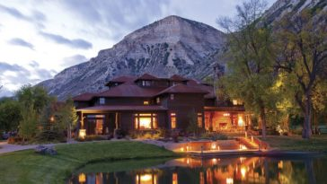 This is a view of the main lodge that has earthy tones to its exterior walls. These are complemented by the warm glow of the indoor and outdoor lights. These are then reflected on the pond. Image courtesy of Toptenrealestatedeals.com.