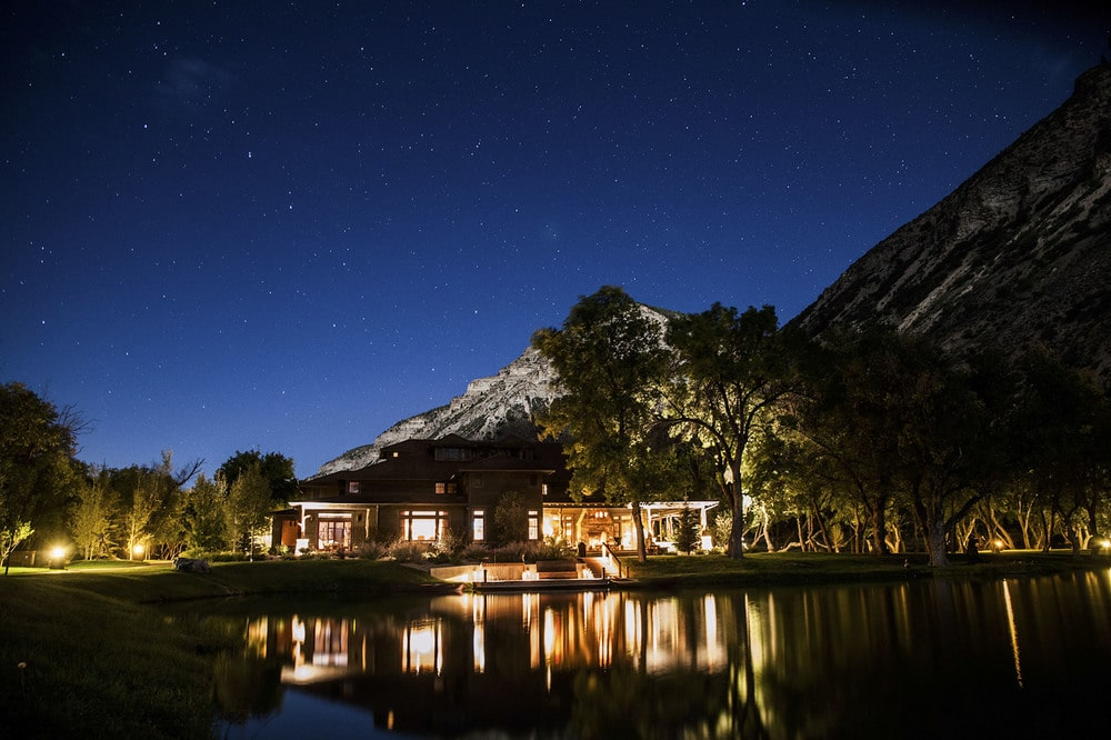 This nighttime view of the back of the house showcases more of the warm glow of the lodge that reflects on the surface of the pond behind it. Image courtesy of Toptenrealestatedeals.com.