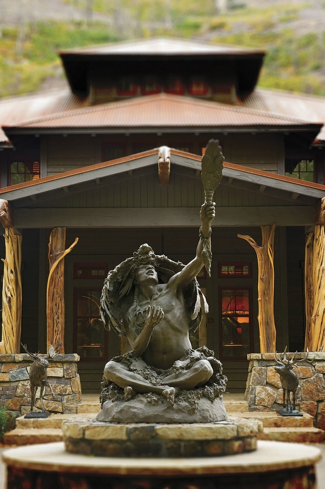 This is a look at the main entrance of the lodge that is adorned with a statue of an ancient hunter along with a couple of deer. You can also see the ceiling of the entrance supported by thick and rustic log pillars. Image courtesy of Toptenrealestatedeals.com.