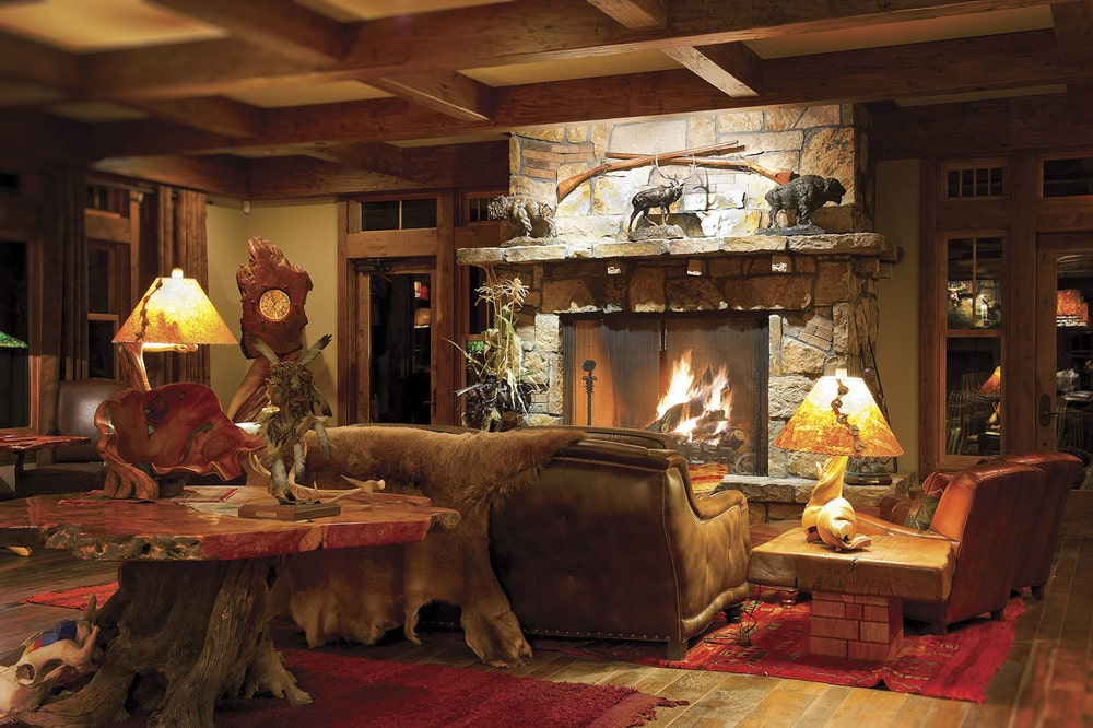 This is the living room with a large stone fireplace across from the comfortable sofa under a wooden coffered ceiling. Image courtesy of Toptenrealestatedeals.com.