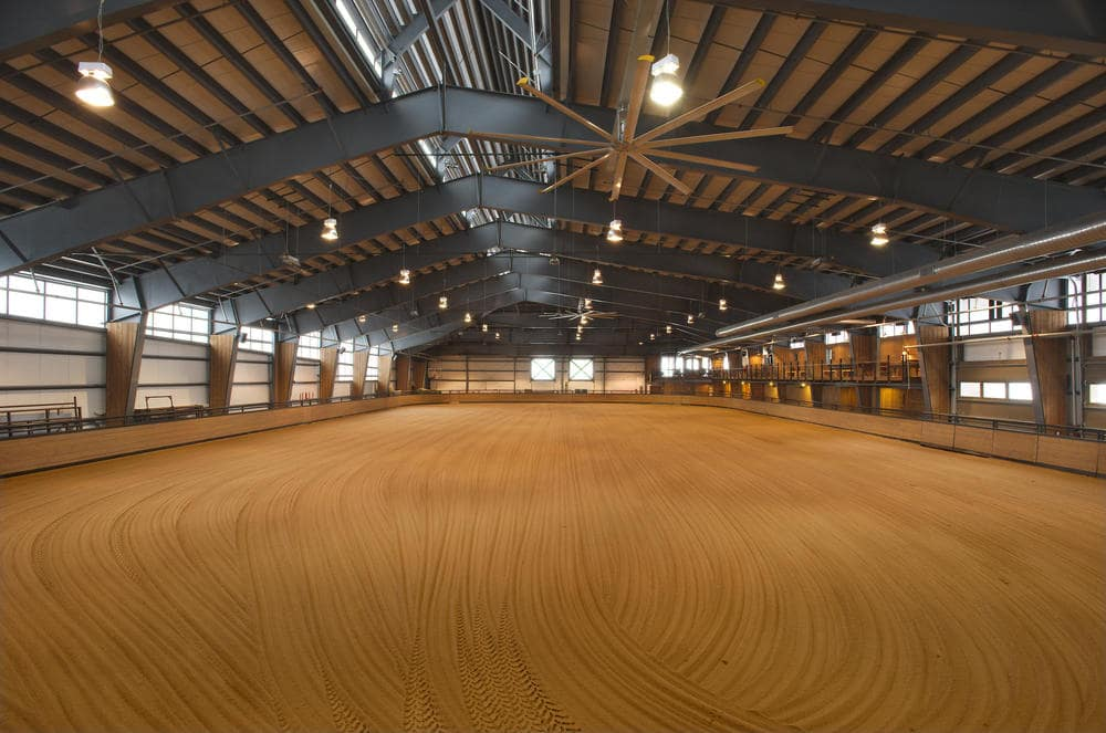 This is vast arena for riding horses. It has a tall cathedral ceiling with large lights and metal beams. Image courtesy of Toptenrealestatedeals.com.