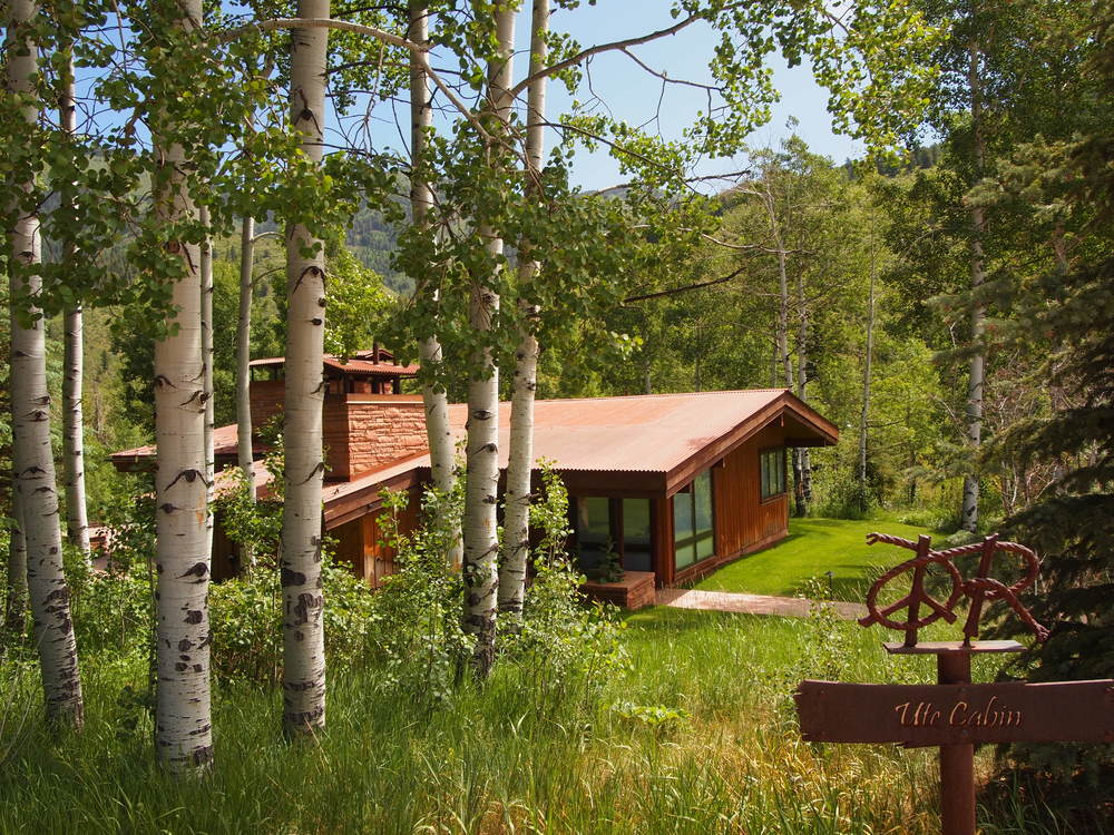This is a look at the cabin with wooden tones on its exteriors that makes it stand out against the surrounding green landscape of trees and shrubs. Image courtesy of Toptenrealestatedeals.com.