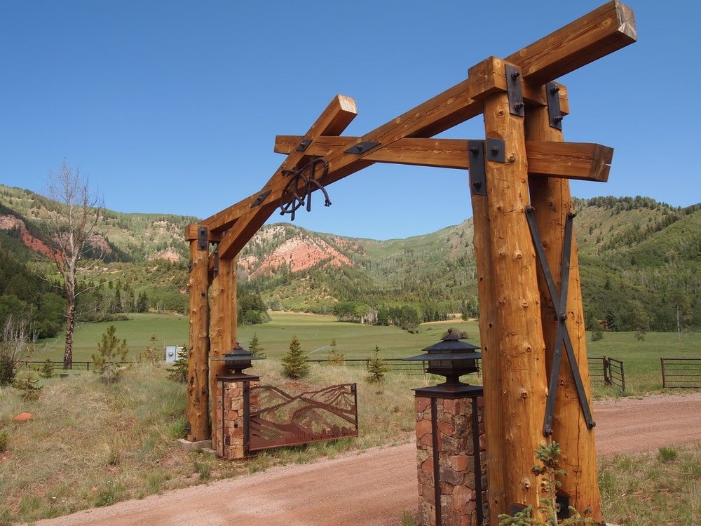 The main gate entrance of the property has a wooden archway adorned with outdoor lamp lights. Image courtesy of Toptenrealestatedeals.com.