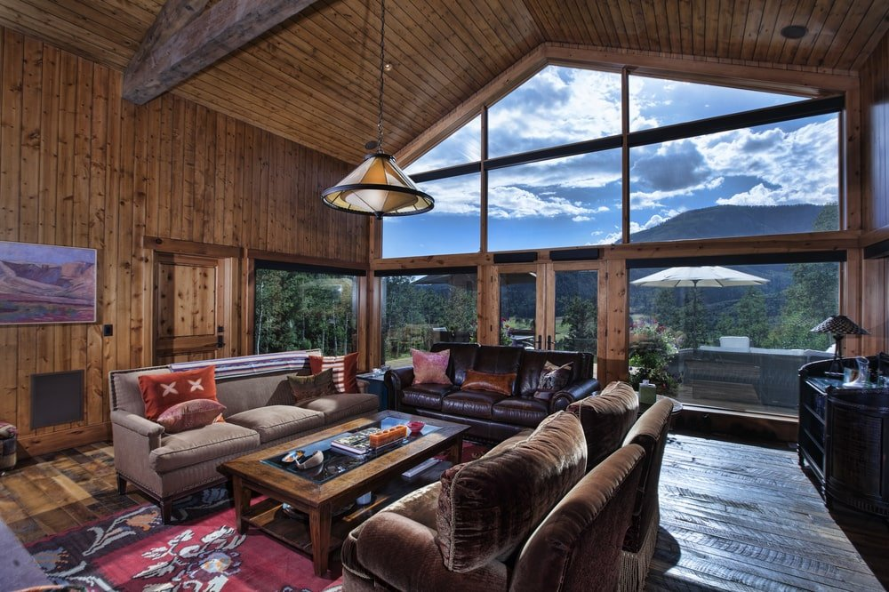 This is the living room with a large glass wall on the far side bringing in natural lighting for the set of sofas surrounding the wooden coffee table. Image courtesy of Toptenrealestatedeals.com.