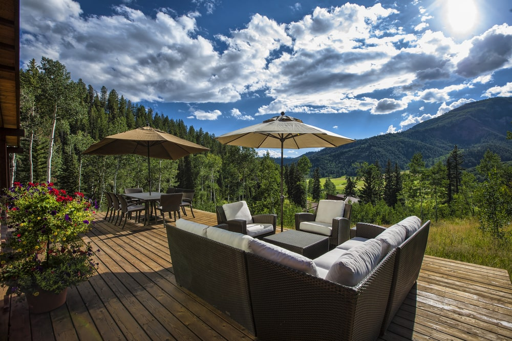 This is the porch with an outdoor sofa set and an outdoor dining set with a sweeping view of the mountains. Image courtesy of Toptenrealestatedeals.com.