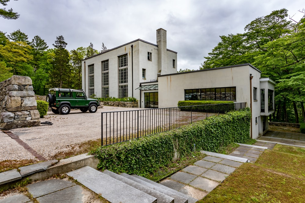 This is the front view of the house that has tall windows that span through floors and a towering chimney in the middle.