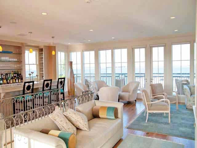 This is the bar of the house surrounded by tall windows with views of the ocean. These brighten up the various beige sofas and armchairs. Image courtesy of Toptenrealestatedeals.com.