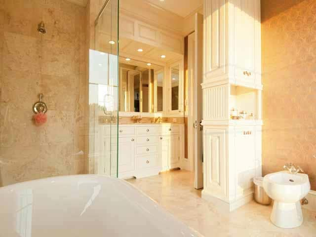 This is a close look at the bathroom with a white porcelain bathtub, beige walls and beige cabinetry that matches with the vanity. Image courtesy of Toptenrealestatedeals.com.