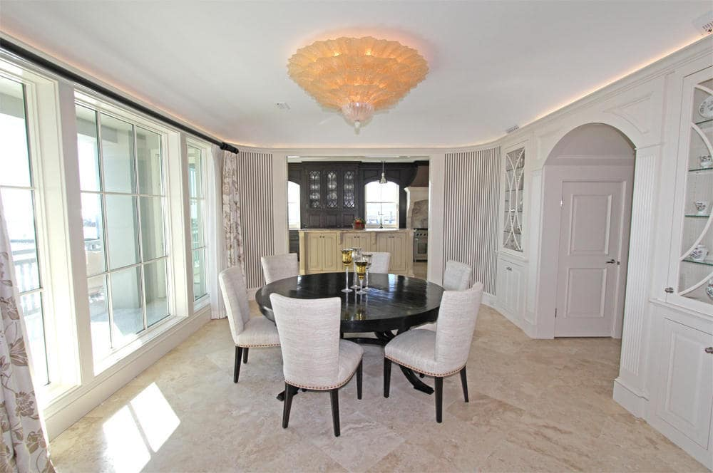 This is a closer look at the formal dining room with a dark round dining table contrasted by the white cushioned chairs. This is topped with a large dome flush-mount lighting. Image courtesy of Toptenrealestatedeals.com.