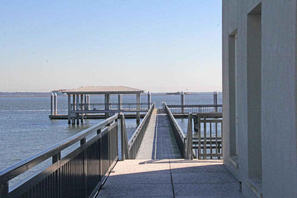 This is a look at the walkway that leads to the private dock at the far end flanked with water. Image courtesy of Toptenrealestatedeals.com.