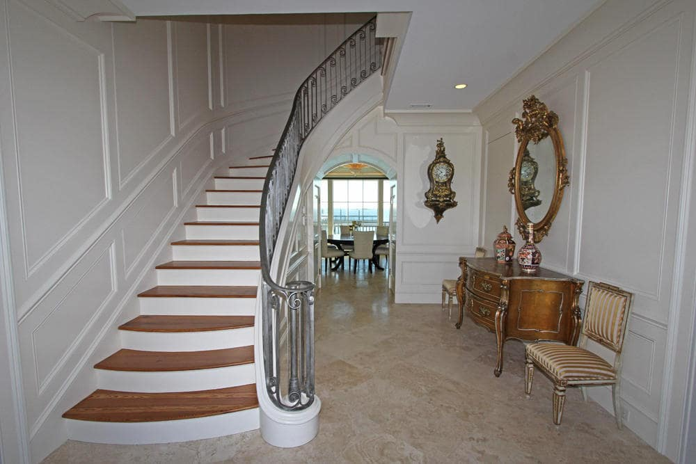 Upon entry of the house, you are welcomed by this grand foyer with a curved staircase and a console table on the side topped with a mirror. Image courtesy of Toptenrealestatedeals.com.