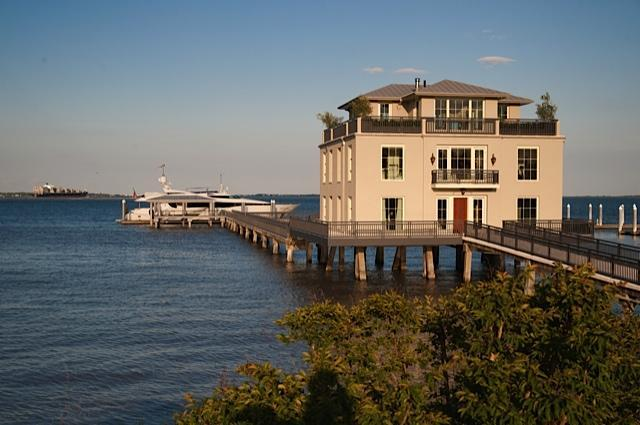 This is a closer look at the front of the house with a walkway leading to the private dock and posts supporting it over the water. Image courtesy of Toptenrealestatedeals.com.