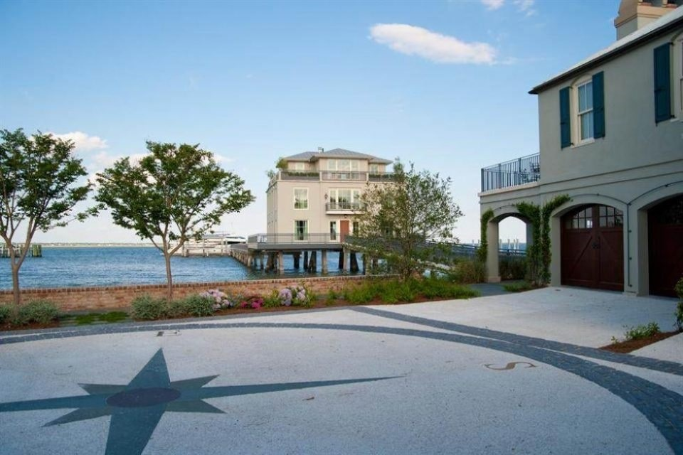 This is a front view of the unique home with beige exterior walls complemented by the surrounding water landscape. Image courtesy of Toptenrealestatedeals.com.
