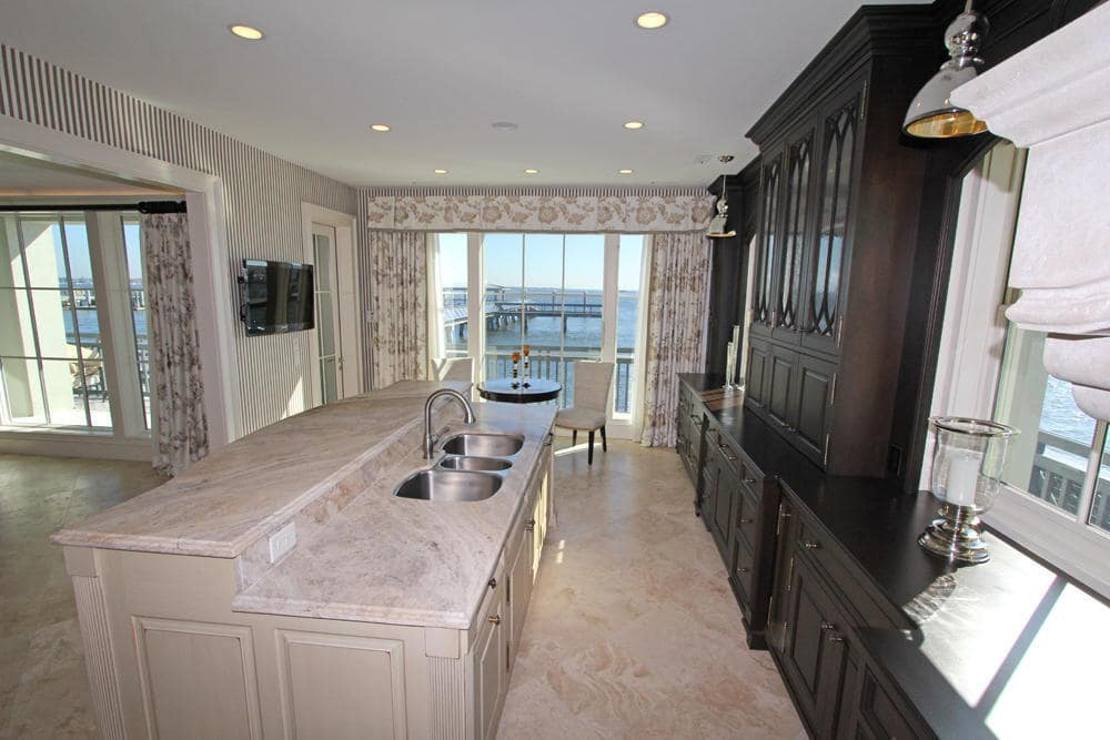 This is the kitchen with a light-toned kitchen island contrasted by the dark wooden cabinetry across from it. Image courtesy of Toptenrealestatedeals.com.