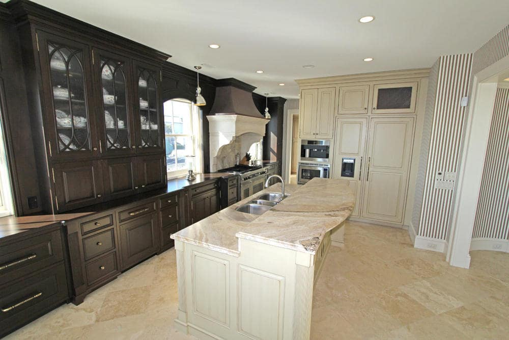 This other look at the kitchen shows the beige cabinetry at the far edge of the kitchen island that matches the beige tone. Image courtesy of Toptenrealestatedeals.com.