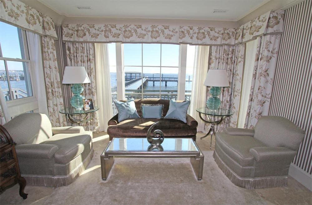 This is the living room with a couple of gray armchairs and a sofa surrounding the glass-top coffee table. Image courtesy of Toptenrealestatedeals.com.