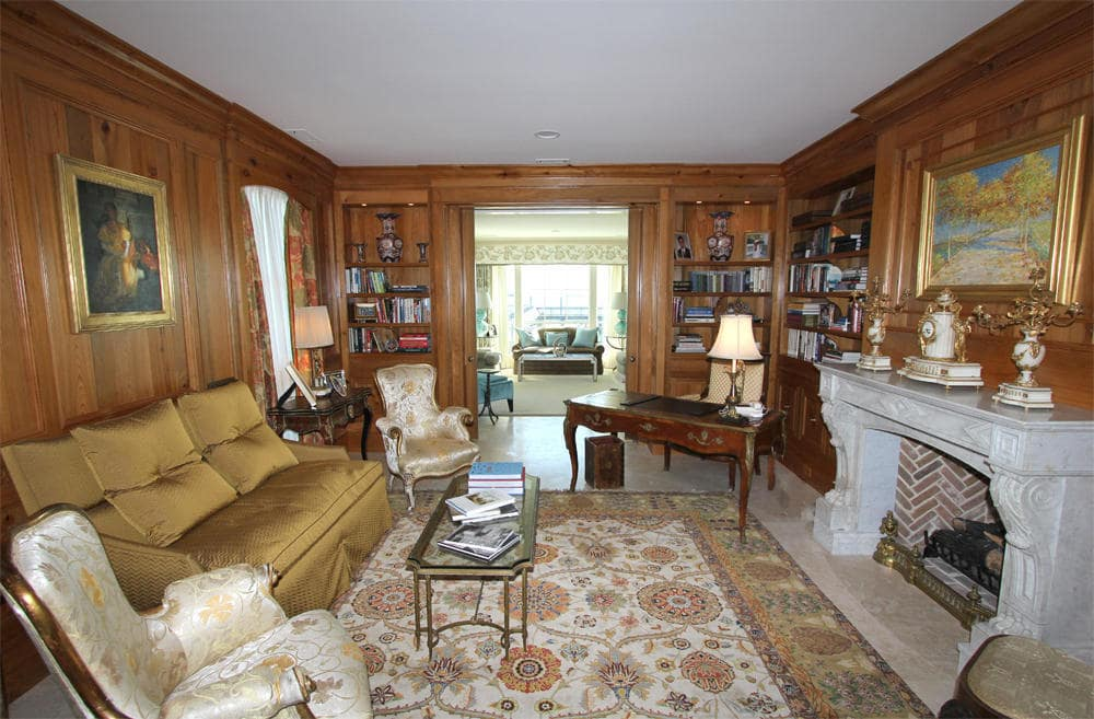 This is the home office with wood-paneled walls that has built-in bookshelves to match the wooden desk at the corner on the side of the fireplace. Image courtesy of Toptenrealestatedeals.com.